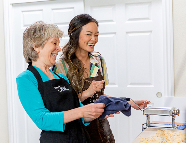 Chef-Joni-sare-student-aprons-laughing-making-pasta-with-hand-crank-pasta-machine-italian-cooking-classes-catering
