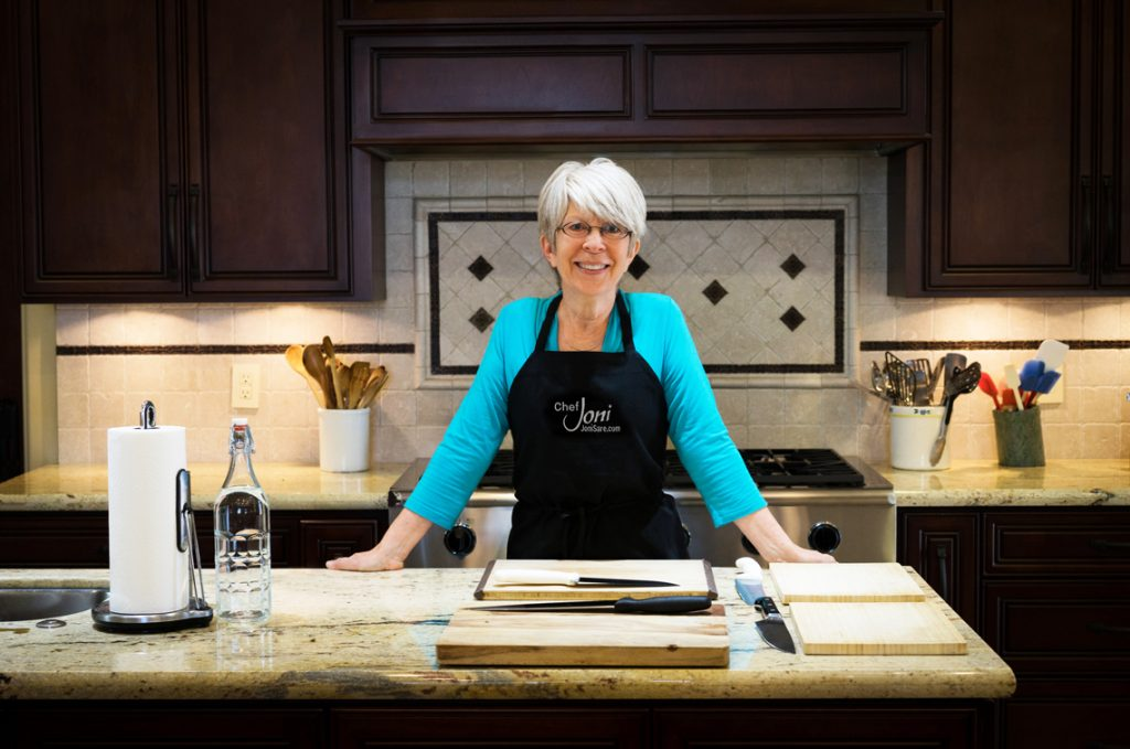 Chef-Joni-sare-with-apron-kitchen-island-knife-cutting-boards-and-6-burner-stove-and-utensils-in-the-background-cooking-class