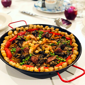 side-view-beautifully-decorated-paella-with-bay-scallops-peas-shrimp-vegetables-dining-table-sangria-wine-dinner-plates-paella-cooking-class