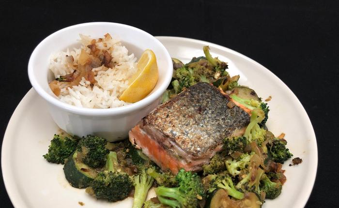 dinner-plate-with-crispy-skin-pan-seared-Salmon-sauteed-Broccoli-Zucchini-Pesto-Rice-caramelized-shallots-Lemon-wedge-ramekin