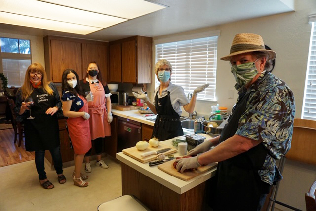 adults-man-and-four-women-wearing-masks-in-the-kitchen-knife-cutting-boards-covid-safe-cooking-class