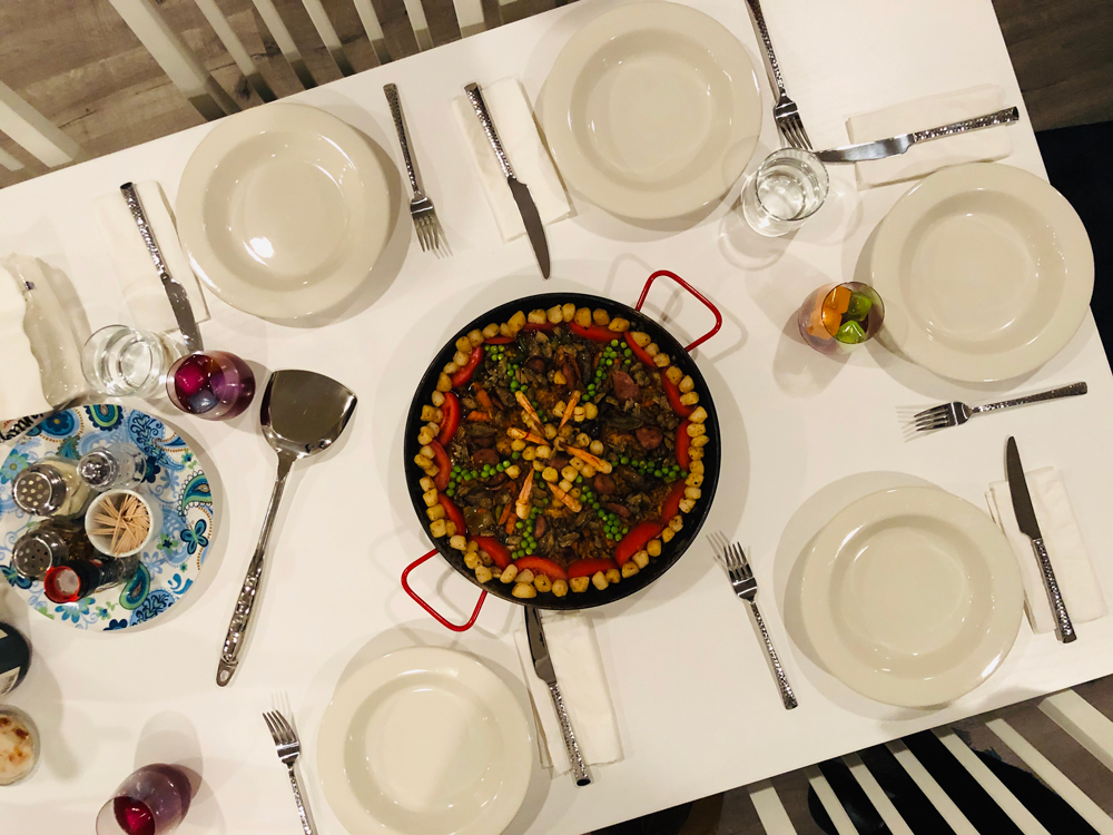 paella-with-bay-scallops-peas-vegetables-dining-table-sangria-wine-dinner-plates-paella-cooking-class-catering-meal-prep