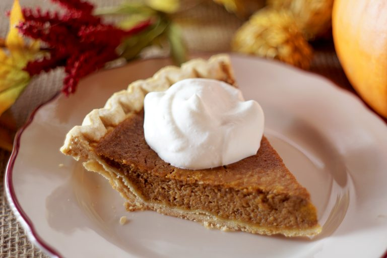 Close up photo of pumpkin pie with whipped cream