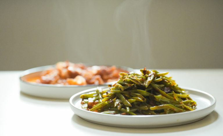 Steaming green beans and stew on white plates