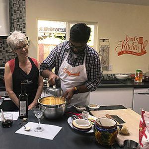 chef-joni-sare-teaching-with-student-using-electric-mixer-kitchen